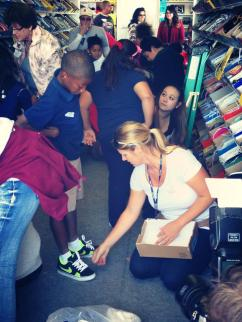 PTWA VP of Communications, Stacy Hoffman helps select a new pair of shoes