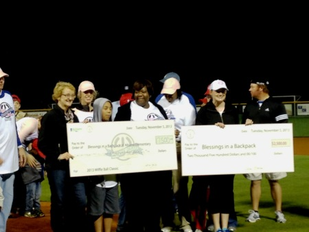 Amy Wilson and Sarah McGirt present two checks to Blessings in a Backpack